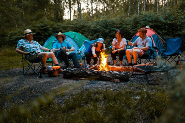 A group of people sitting around the campfire in front of a tent - jokes about camping