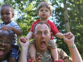 Two dads with their kids on shoulders Sussex family camping weekend
