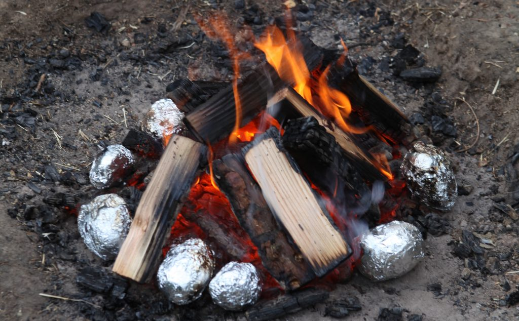 Jacket potatoes cooking on the campfire - one of the easiest campfire dinners