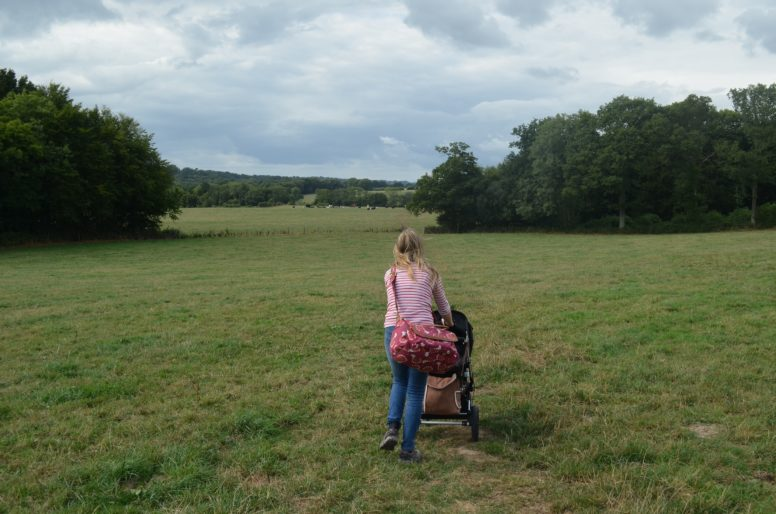 A camper with a wheelbarrow walking through a field during a spring glamping trip with time to return