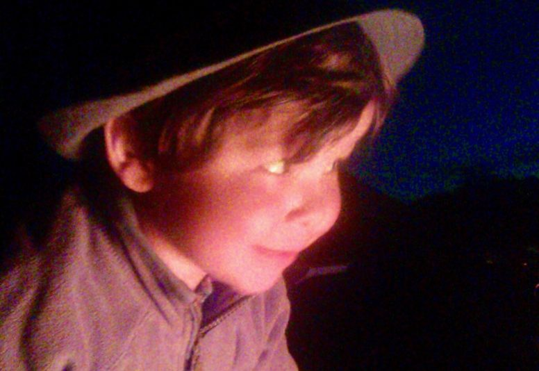 A little boy in the glow of a campfire - camping games for kids can include campfire storytelling