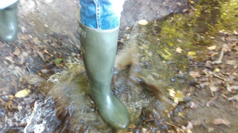 A welly splashing in a puddle proving you can still go for a walk whilst camping in the rain - if you've got the right gear!