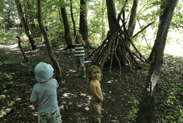 Children building a den in the woodland at our Sussex family glamping site The Secret Campsite Wild Boar Wood