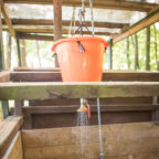 Woman in outdoor bucket shower at glamping site in Sussex